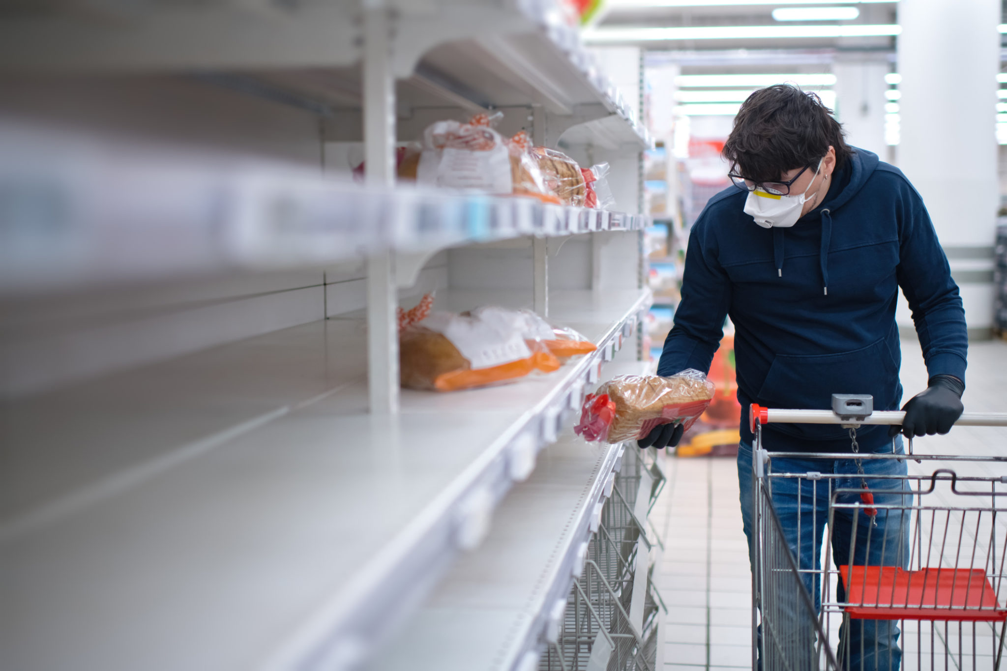 Man's hands in protective gloves searching bread on empty shelves in a groceries store